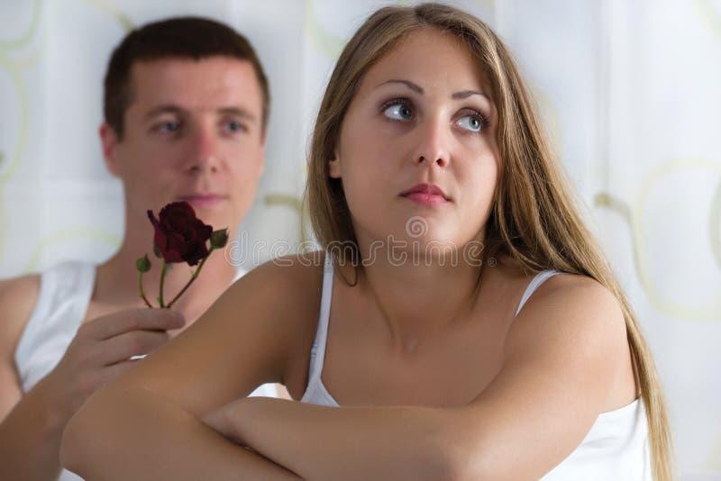 El hombre quiere donar a una mujer de la rosa que esté enojada foto de archivo libre de regalías