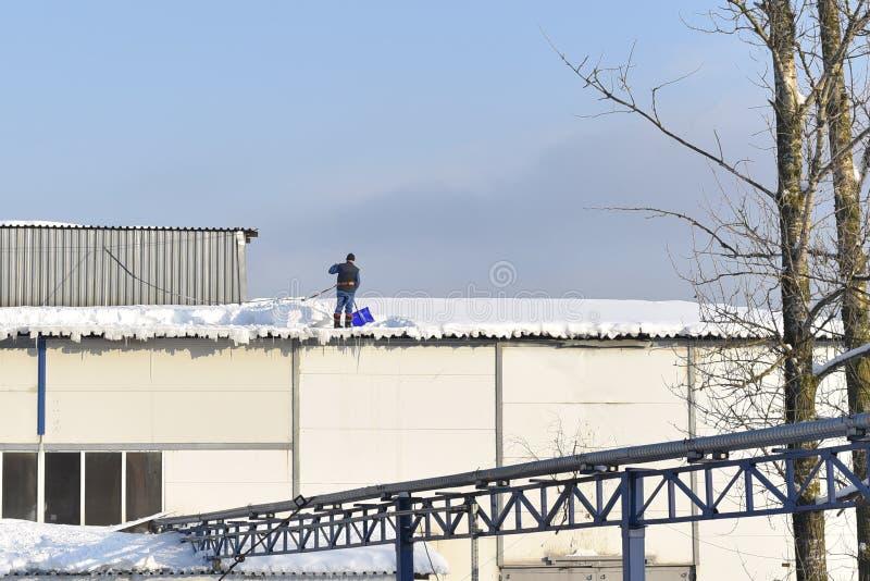 El hombre quita nieve del tejado de un edificio fotografía de archivo libre de regalías