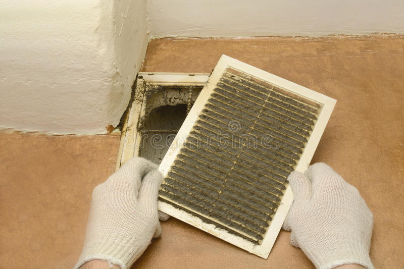 El hombre quita parrillas de la ventilación del polvo imagenes de archivo
