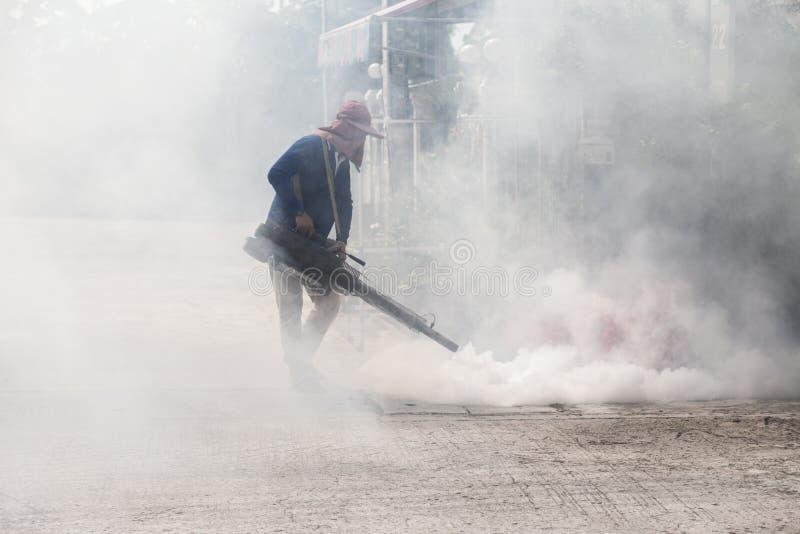 El hombre realiza empañarse en el pueblo para el anti-mosquito foto de archivo