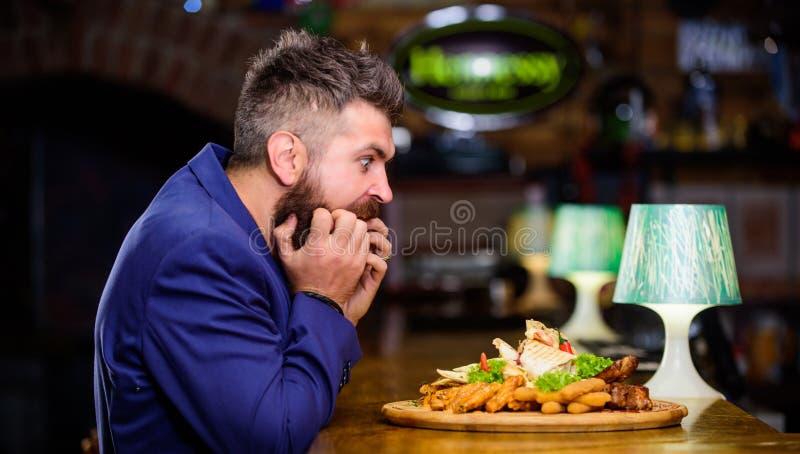 El hombre recibió la comida con los pescados fritos de la patata pega la carne Disfrute de la comida Alto bocado de la caloría Co foto de archivo