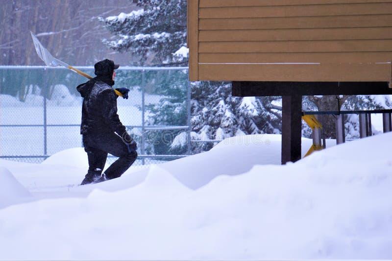 El hombre recorre con dificultad a través de nieve profunda con la pala fotos de archivo libres de regalías
