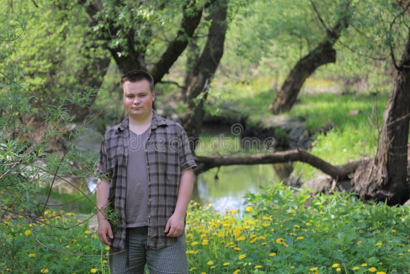 El hombre regordete joven se coloca con el suyo de nuevo al r?o En el parque entre el follaje verde claro foto de archivo