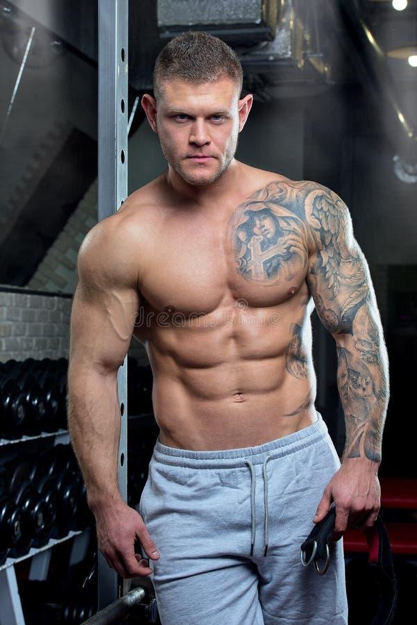 El hombre relajado fuerte destrozado descamisado muscular con los ojos azules y el tatuaje presenta en pantalones de un gris en u foto de archivo libre de regalías