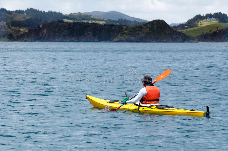 El hombre rema un kajak del mar foto de archivo