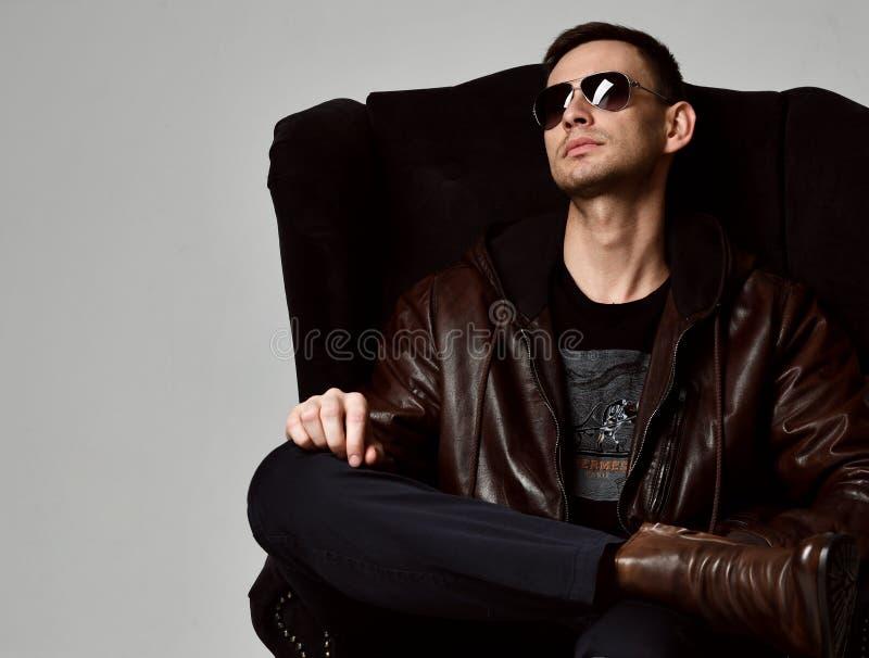 El hombre rico acertado joven en la chaqueta de cuero del marrón negro de la camiseta y botas de cuero marrones se sienta en buta imagen de archivo