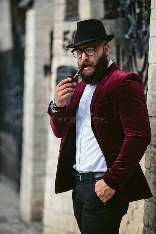 El hombre rico con una barba fuma el cigarrillo electrónico fotografía de archivo