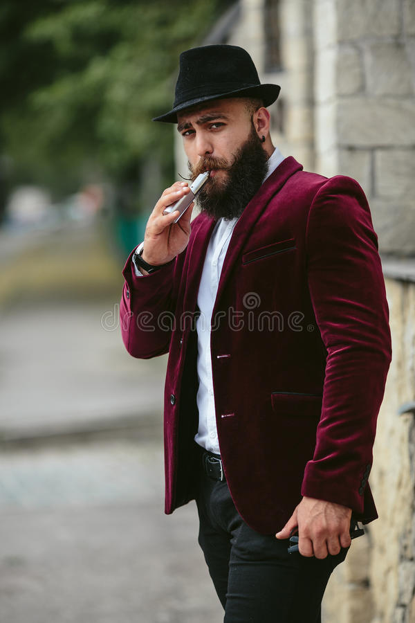 El hombre rico con una barba fuma el cigarrillo electrónico imagen de archivo libre de regalías
