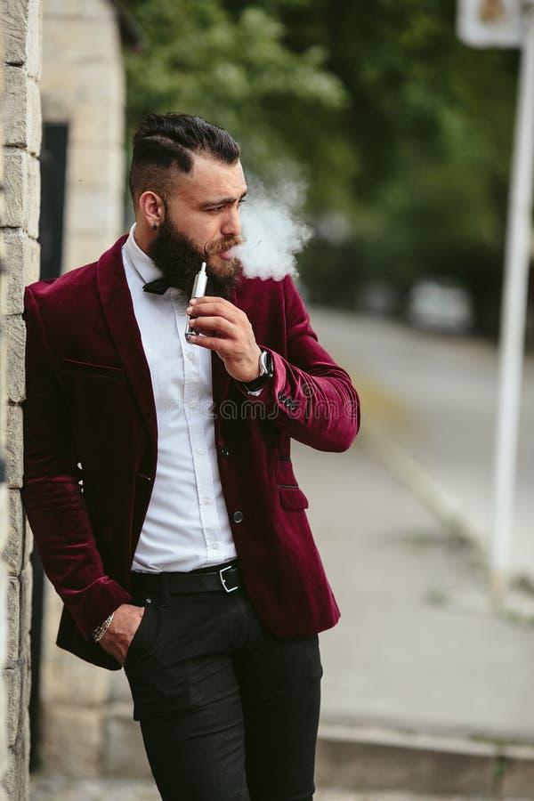 El hombre rico con una barba fuma el cigarrillo electrónico imágenes de archivo libres de regalías