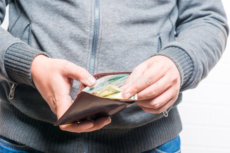 El hombre rico cuenta el dinero en un monedero, primer fotografía de archivo libre de regalías