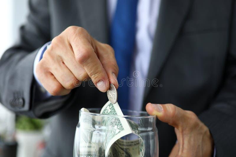 El hombre rico en traje y lazo puso la moneda adicional en el tarro por completo de dólares americanos imagen de archivo