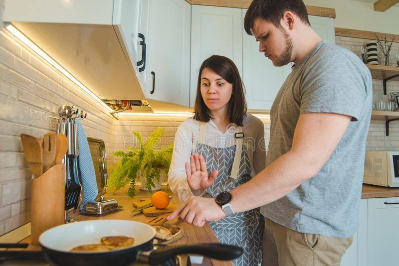 El hombre roba la comida mientras que mujer que hace el desayuno foto de archivo