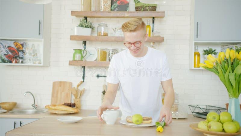 El hombre rubio hermoso está haciendo el desayuno para su novia por la mañana en la cocina fotografía de archivo libre de regalías