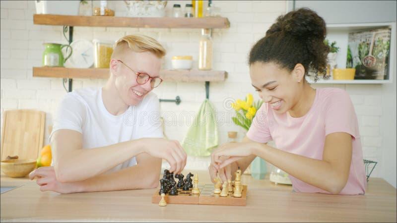 El hombre rubio joven está jugando a ajedrez con la mujer joven afroamericana fotos de archivo