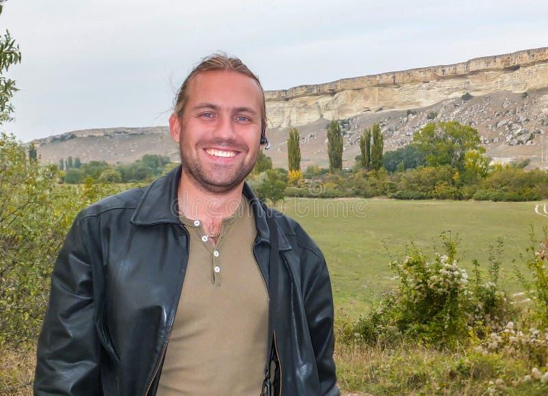El hombre rubio joven hermoso está sonriendo contra de los acantilados blancos del soporte Ak-Kaya imagen de archivo libre de regalías