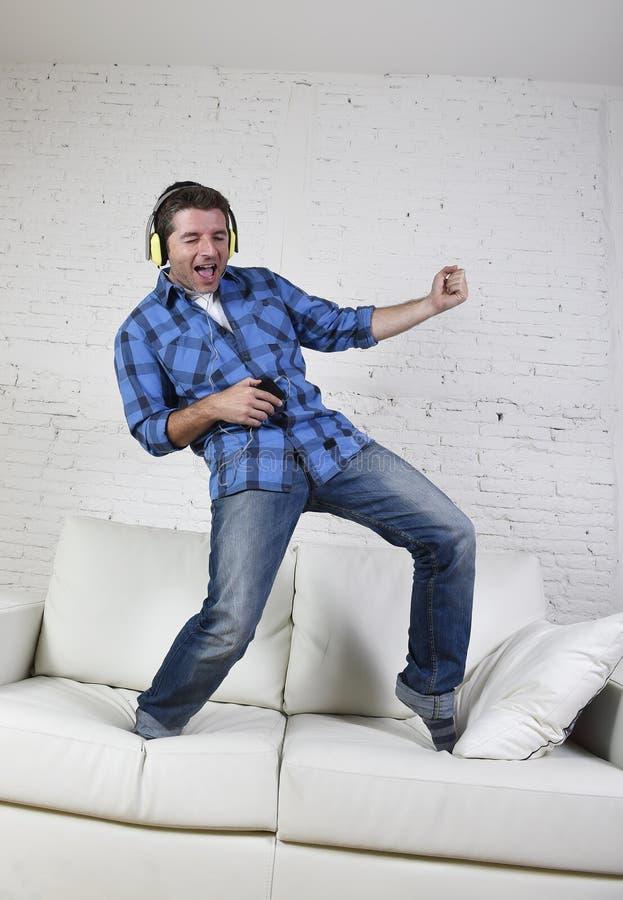 el hombre 20s o 30s saltó en el sofá que escuchaba la música en el teléfono móvil con los auriculares que jugaban Air Guitar imagen de archivo libre de regalías