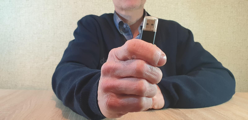 El hombre saca de su memoria USB del bolsillo El hombre lleva a cabo memoria USB imagen de archivo libre de regalías
