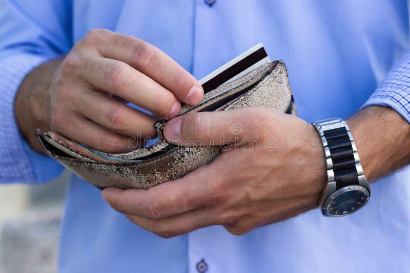 El hombre saca una tarjeta de crédito de la cartera fotos de archivo libres de regalías