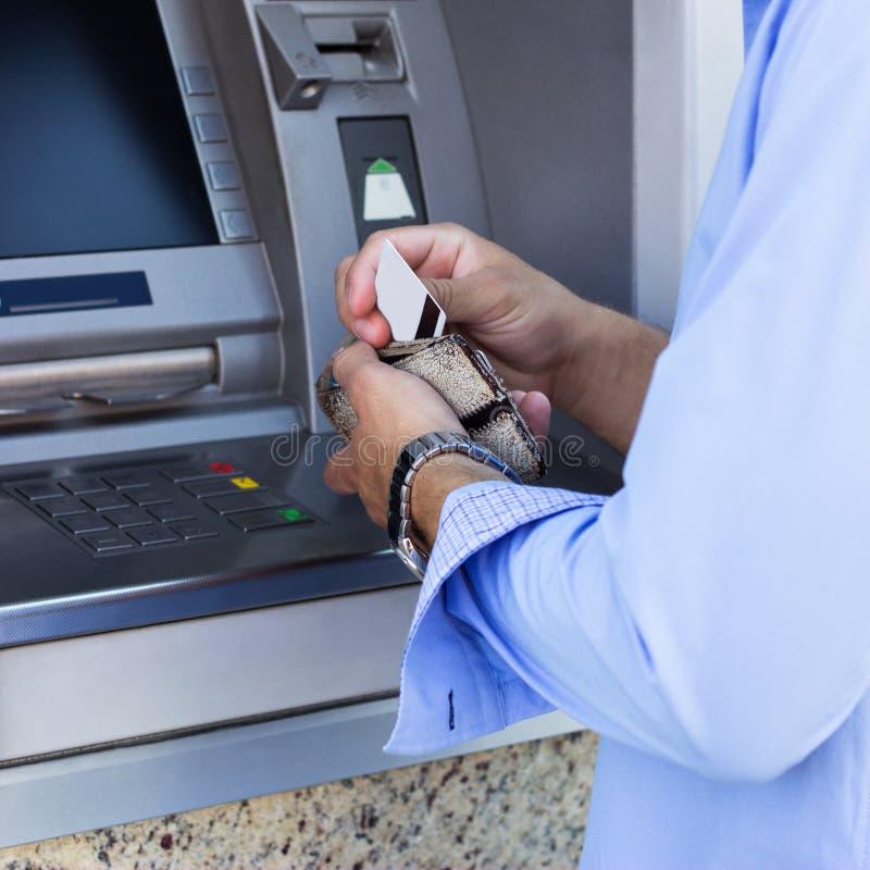 El hombre saca una tarjeta de crédito de su cartera imágenes de archivo libres de regalías