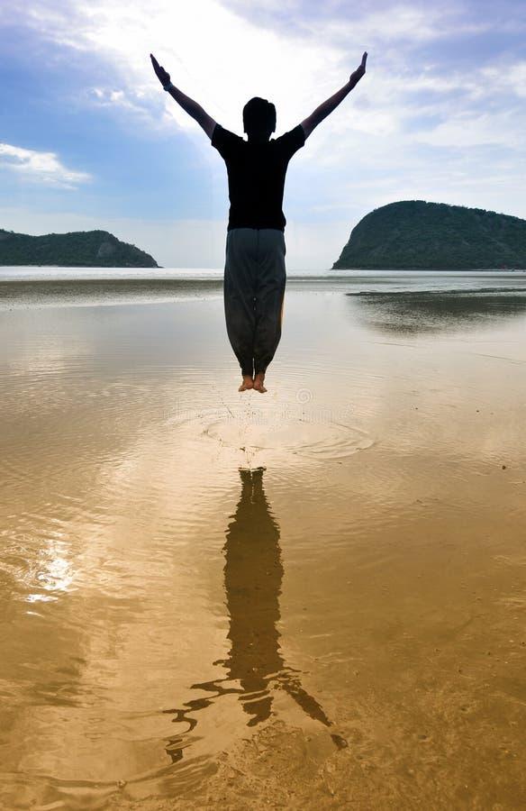 El hombre salta en la playa imagenes de archivo