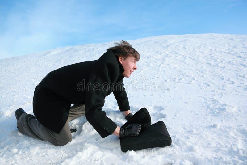 El hombre se arrastra en nieve con la cartera imagen de archivo