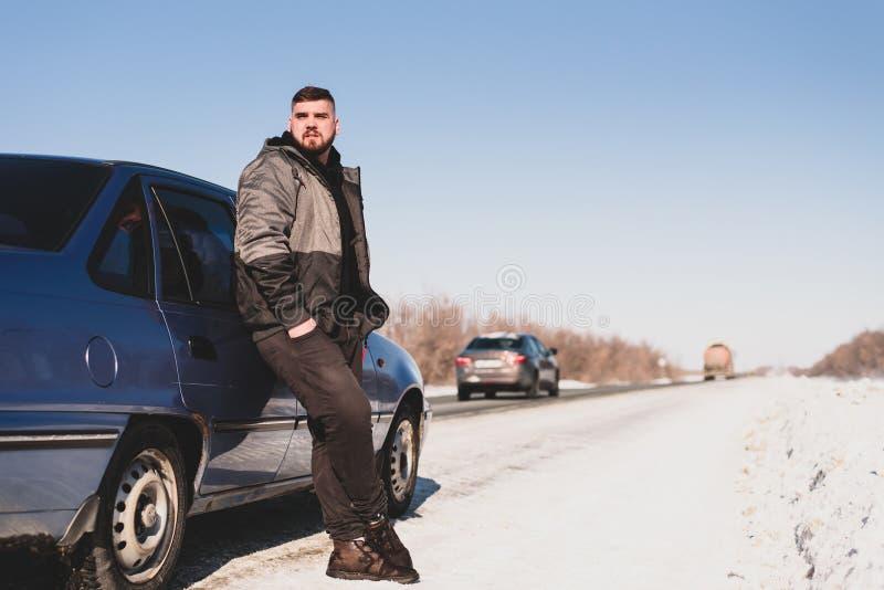 El hombre se coloca cerca de su coche quebrado en invierno imagenes de archivo