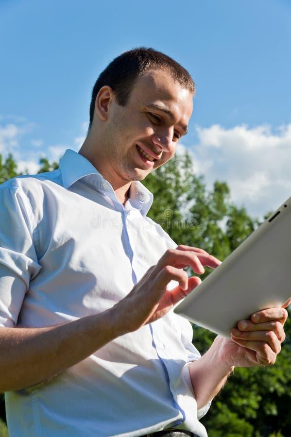 El hombre se coloca con la tableta imagen de archivo libre de regalías