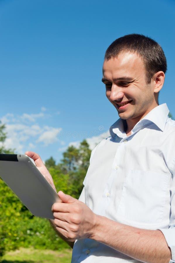 El hombre se coloca con la tableta imagen de archivo