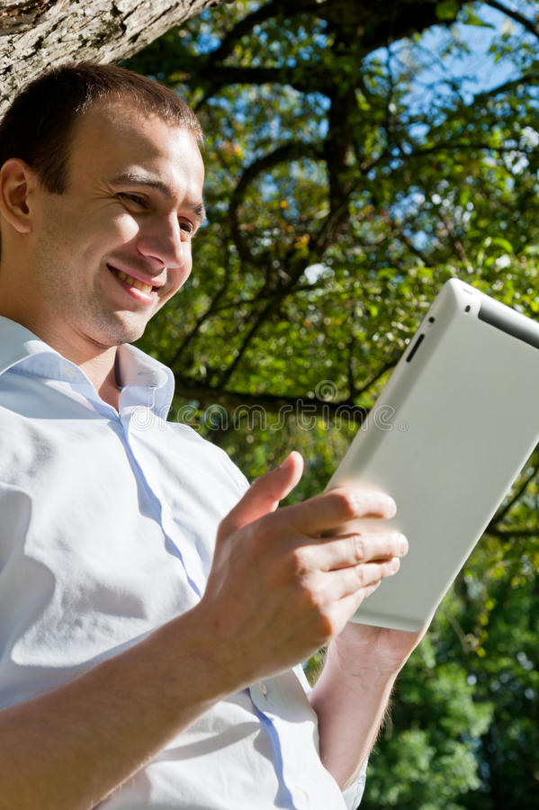 El hombre se coloca con la tableta cerca del árbol imagenes de archivo