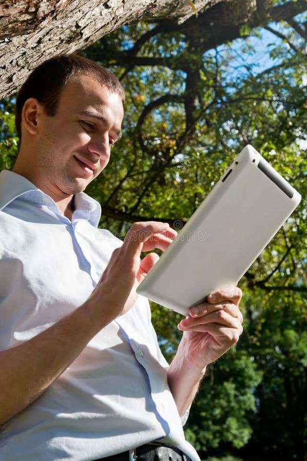 El hombre se coloca con la tableta cerca del árbol fotografía de archivo libre de regalías