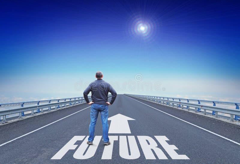 El hombre se coloca en un camino que va al futuro y mira en la estrella rectora sobre horizonte imagen de archivo
