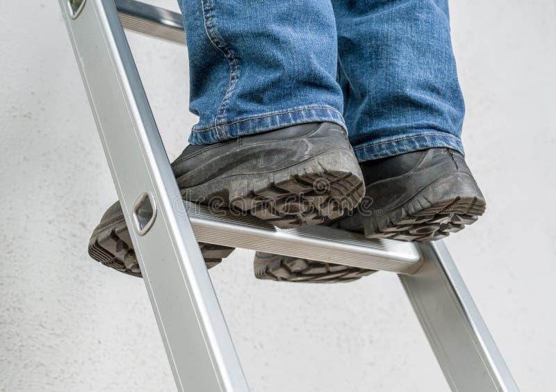El hombre se coloca en una escalera foto de archivo