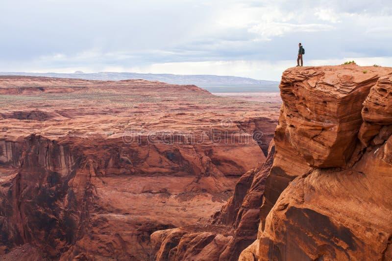 El hombre se coloca encima de una montaña Caminante con la mochila que se coloca en una roca, disfrutando de la opinión del valle imagen de archivo