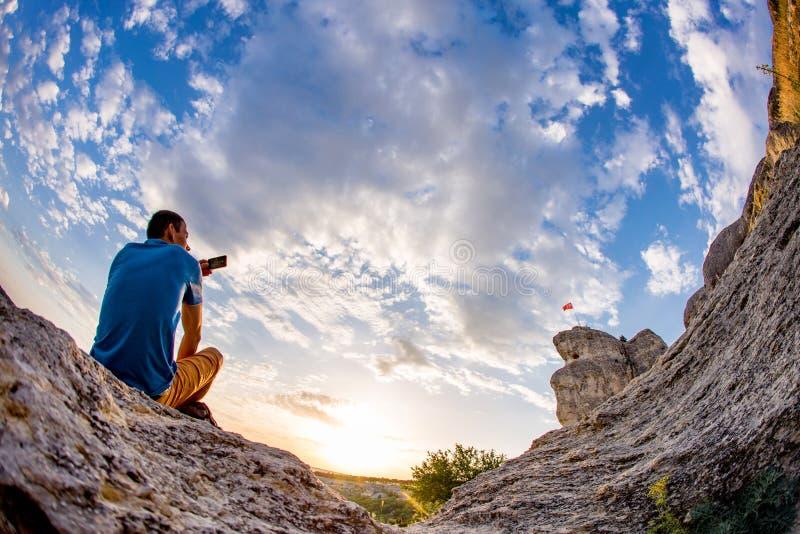 El hombre se coloca enfrente de fondo del cielo de la nube fotos de archivo libres de regalías
