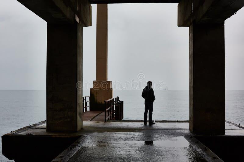 El hombre se coloca solo en un embarcadero del mar en mún tiempo Aire de niebla foto de archivo