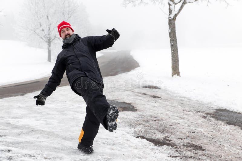 El hombre se está deslizando en un camino helado foto de archivo libre de regalías