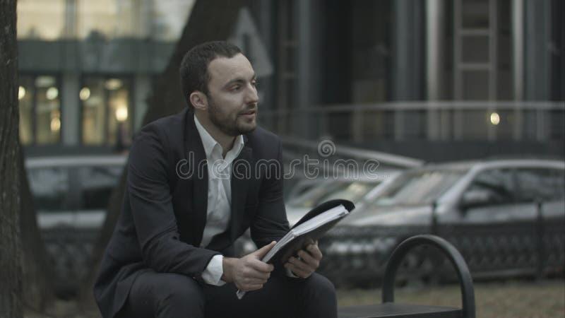 El hombre se está sentando en un banco en parque y descontentado leyendo el plan empresarial foto de archivo libre de regalías