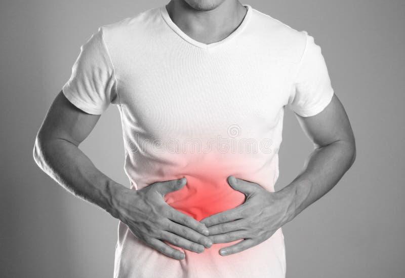 El hombre se está sosteniendo el estómago Dolor abdominal El hogar es hola fotografía de archivo