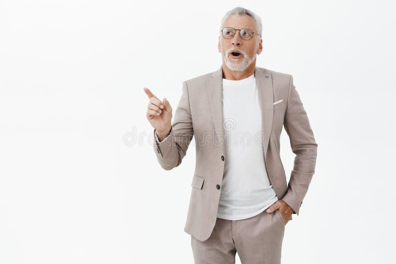 El hombre se pregunta cómo los cambios rápidos del mundo Viejo modelo masculino encantador impresionado y encantado con la tenenc foto de archivo