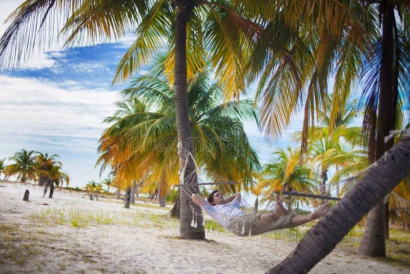 El hombre se relaja en la playa en hamaca fotos de archivo