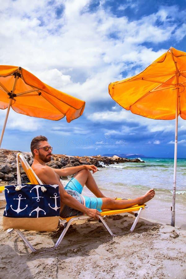 El hombre se relaja en la playa en una silla debajo del paraguas imagenes de archivo