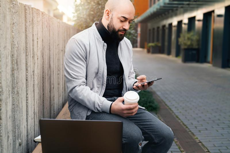 El hombre se sienta en banco y el smartphone de las aplicaciones durante descanso para tomar café, es después ordenador portátil  foto de archivo