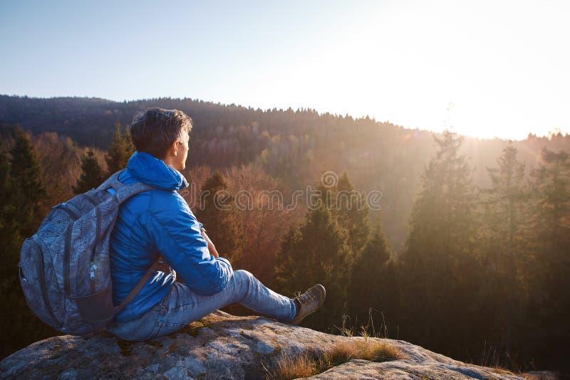 El hombre se sienta en el borde del acantilado contra el fondo de la salida del sol fotografía de archivo