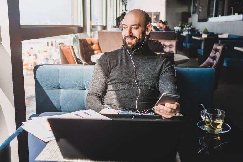 El hombre se sienta en café delante del ordenador portátil, escucha la música en auriculares con smartphone El inconformista del  imagen de archivo libre de regalías
