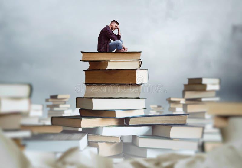 El hombre se sienta en una pila de libros imagen de archivo