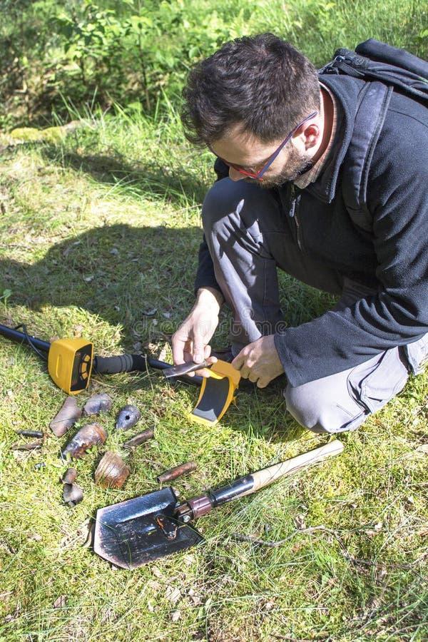 El hombre se sostiene en su mano que un objeto encontró en la tierra Un detector de metales y una pala mienten al lado de él fotografía de archivo libre de regalías