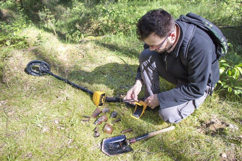 El hombre se sostiene en su mano que un objeto encontró en la tierra Un detector de metales y una pala mienten al lado de él fotos de archivo libres de regalías