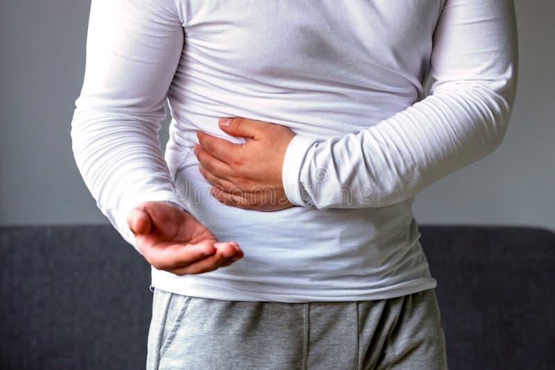 El hombre se sostiene el estómago, píldoras foto de archivo