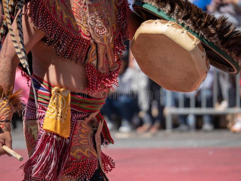 El hombre se vistió en golpes aztecas tradicionales del atuendo en un tambor durante la mañana fotos de archivo