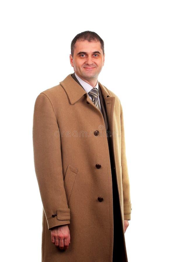 El hombre se vistió en la capa marrón clara aislada en blanco foto de archivo libre de regalías